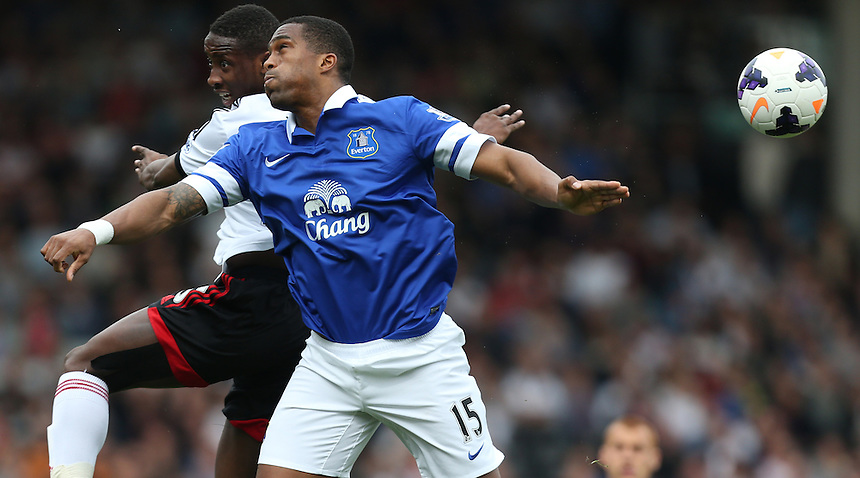 Fulham's Moussa Dembele despite the attentions of  Everton's Sylvain Distin<br /> <br /> Photo by Kieran Galvin/CameraSport<br /> <br /> Football - Barclays Premiership - Fulham v Everton - Sunday 30th March 2014 - Craven Cottage - London<br /> <br /> &copy; CameraSport - 43 Linden Ave. Countesthorpe. Leicester. England. LE8 5PG - Tel: +44 (0) 116 277 4147 - admin@camerasport.com - www.camerasport.com