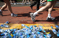 17 APR 2011 - LONDON, GBR - Runners pass empty water bottles during the London Marathon (PHOTO (C) NIGEL FARROW)