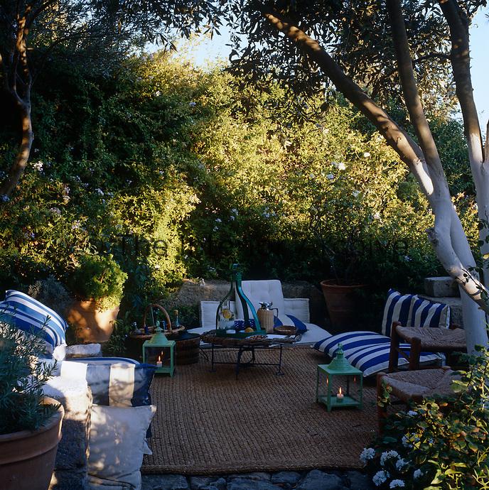 An al fresco comfortable seating area hidden in the garden of a Mediterranean villa