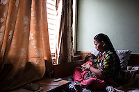 "Nepal - Kathmandu - Him Kumari Yongan, 25, breasfeeding  her 3-year-old child Noshan Tamang in a guesthouse close to Kathmandu Airport. Yongan's husband, 26-year-old Narabaj Tamang, died last March due to an acute respiratory failure in Qatar, where he had been employed as a glass cleaner, instead of security guard as stated in the contract he signed in Nepal. Tamang had left his country 21 months before, quitting his post of English teacher in a government school where he was earning a little more than 30 dollars per month. Now, Yongan will have to find a way to provide for his kid. ""I have no idea what to do now"" she says in despair. ""We just have a small piece of farmland to sustain ourselves""."