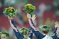 26 August 2004: Abby Wambach and Brandi Chastian with their flowers during the ceremony after defeating Brazil during the gold medal game at Karaiskakis Stadium in Athens, Greece.   USA defeated Brazil, 2-1 in overtime.   Credit: Michael Pimentel / ISI.