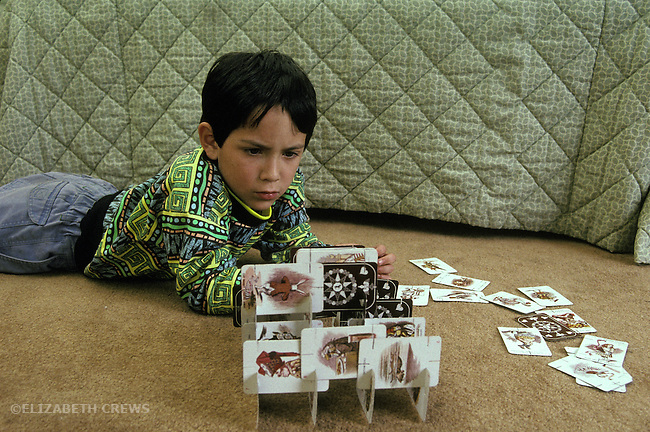 "San Diego CA Latino boy, 6, concentrating on building with ""house of cards"""