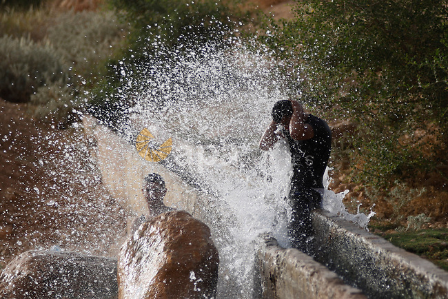 Palestinians slide in a water canal used for irrigation to cool off as temperatures soar in the West Bank city of Jericho to 44 degrees Celsius (111 Fahrenheit), on May 27, 2015. Photo by Shadi Hatem