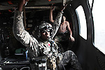 "Staff Sgt. Rakheem Francis, 24, of Queens, N.Y., a flight medic with the 101st Combat Aviation Brigade's ""Shadow ""Dustoff"", looks out the window of a helicopter after treating an Afghan soldier who died moments after arriving at the NATO hospital at Kandahar Airfield, Afghanistan. The Afghan soldier sitting behind Francis suffered light wounds during the same ambush and was being transported to a nearby Afghan facility. Sept. 19, 2010. DREW BROWN/STARS AND STRIPES"