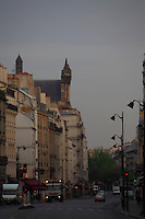A view of rue Saint Antoine in the Marais, Paris, at the sunrise, with the car lights, some street lamps, some trees on the background, a mural and the roof of the Saint Paul and Saint Louis church surrounded by the old buildings. Digitally Improved Photo.