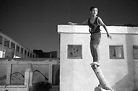 A boy balances on a branch as he plays outside a polling station in Cairo, during the two-day run-off. June 16th, 2012. Cairo, Egypt.
