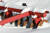 side view of disc harrows partially buried under snow