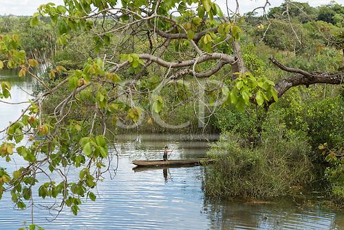 Xingu Indigenous Park, Mato Grosso State, Brazil. Posto Leonardo. A young boy paddles a dugout canoe.