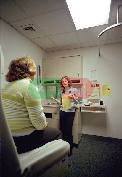 Young female internal medicine resident physician listening to, speaking with patient in examination room