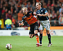 Dundee Utd's Gary Mackay-Steven is bundles off the ball by Dundee's Gary Irvine.