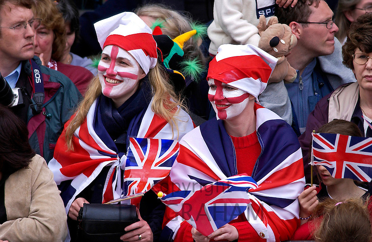 Enthusiasts wearing Union Jack flags and England flag symbols painted on their faces, London, England