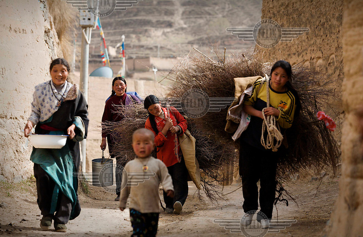 Women and children carry bundles of branches outside a walled village near the town of Tongren.