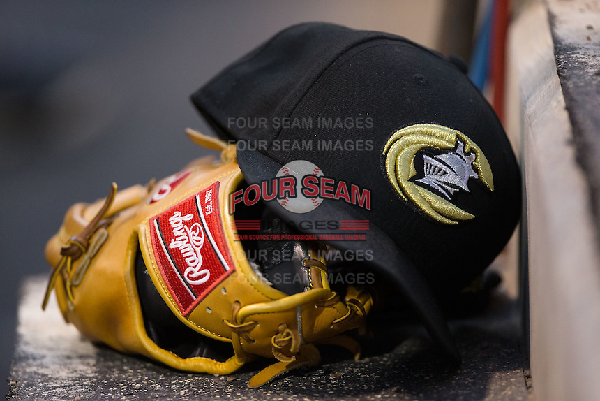 A Charlotte Knights cap sits on top of a glove in the home dugout during the game against the Columbus Clippers at BB&T BallPark on May 27, 2015 in Charlotte, North Carolina.  The Clippers defeated the Knights 9-3.  (Brian Westerholt/Four Seam Images)