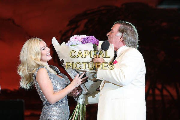 KATHERINE JENKINS & SIR TERRY WOGAN.The BBC Proms In The Park at Hyde Park, London, England..September 12th, 2009.stage concert live gig performance music half length silver sequins sequined dress microphone singing white jacket flowers bouquet profile .CAP/MAR.© Martin Harris/Capital Pictures.
