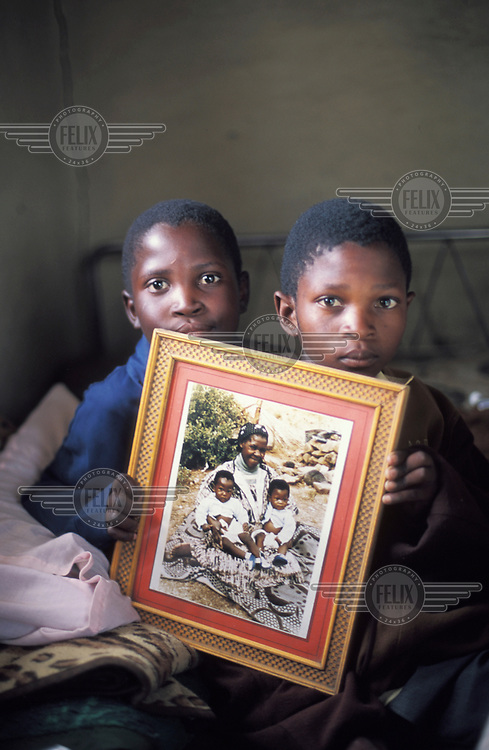 AIDS orphans, holding a photograph of themselves with their mother just before she died.