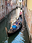 Tourists take a gondola ride on a canal in Venice, Italy.