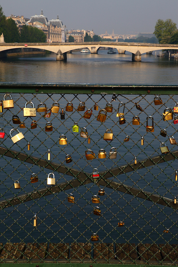 The romantic padlocks which the lovers are used to put onto the railing of the Pont des Arts (bridge of the arts) in Paris in foreground, with the view towards the center of the town in the background. Digitally Improved Photo.