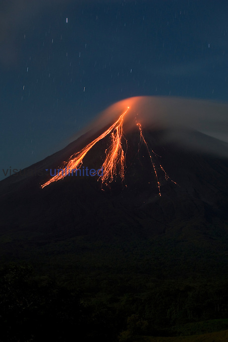 Arenal Volcano ,5356 ft, 1633 m, reveals star trails in the sky and lava flows cascading down the sides. This is an active stratovolcano that has had numerous eruptions since 1968 when its first major eruption killed ~100 people. Costa Rica.
