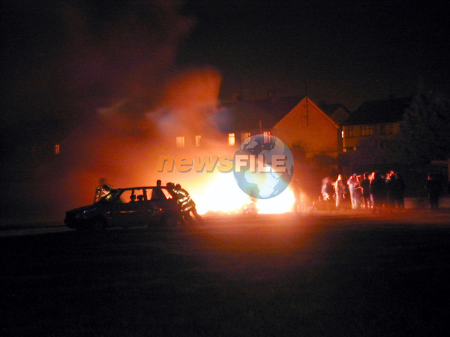 Gardai recover a car which was being rolled into the bonfire by youths in Moneymore..NO BYLINE PLEASE