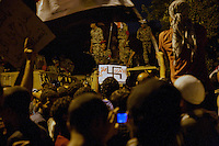 EGITTO, IL CAIRO 9/10 settembre 2011: assalto all'ambasciata israeliana. Migliaia di manifestanti egiziani, ancora infuriati per l'uccisione di cinque guardie di frontiera egiziane da parte dell'esercito israeliano, hanno fatto irruzione nella sede diplomatica israeliana e sono stati poi sgomberati da esercito e polizia egiziana. Nell'immagine: folla di manifestanti ed esercito sui blindati. Tra i manifestanti qualcuno mostra un cartello con la svastica.<br /> Egypt attack to the Israeli embassy  Attaque &agrave; l'ambassade israelienne Caire