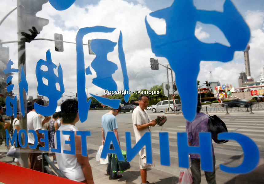 Pedestrians waiting to cross a street seen from the inside of a China Telecom phone booth in Shanghai, China..