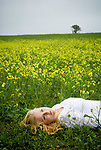 Blonde woman in white shirt laying field with yellow flowers