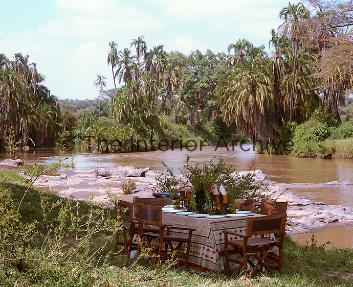 A covered table is laid for lunch overlooking a point in the river where the water breaks over the rocks