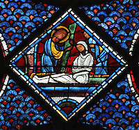 Christ raises the stone from the tomb and Lazarus is resurrected, still wrapped in his shroud, the Resurrection of Lazarus, from the Life of Mary Magdalene stained glass window, 13th century, in the nave of Chartres cathedral, Eure-et-Loir, France. Chartres cathedral was built 1194-1250 and is a fine example of Gothic architecture. Most of its windows date from 1205-40 although a few earlier 12th century examples are also intact. It was declared a UNESCO World Heritage Site in 1979. Picture by Manuel Cohen