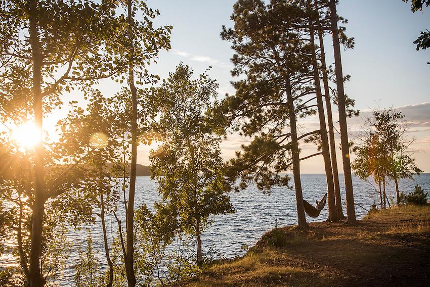 Person in hammock along shore of  Lake Superior at Presque Isle Park, Marquette, Michigan.