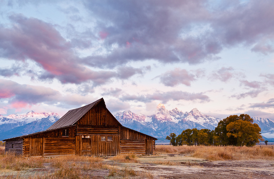 Purple and orange light fills the clouds and illuminates the Teton mountains during sunrise.