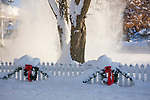 Idaho, Dalton Gardens. Coeur d' Alene. Wreaths with red bows, and Christmas garland decorate a white picket fence in a white snowy landscape while snow falls from the tree branches.
