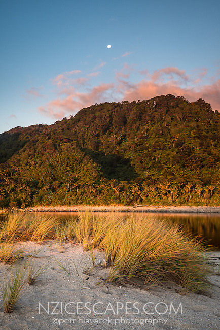 Sunset on beach with Kohaihai River and moon near Karamea, Kahurangi National Park, Buller Region, West Coast, New Zealand