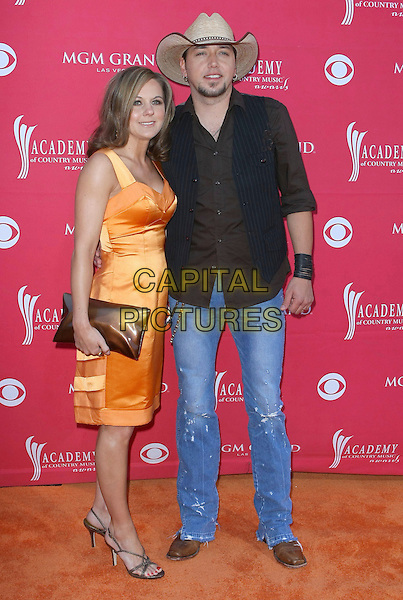 JASON & JESSICA ALDEAN .44th Annual Academy Of Country Music Awards held at the MGM Grand Garden Arena, Las Vegas, Nevada, USA, .5th April 2009. .full length black shirt cowboy hat jeans orange dress silk satin .CAP/ADM/MJT.©MJT/Admedia/Capital Pictures