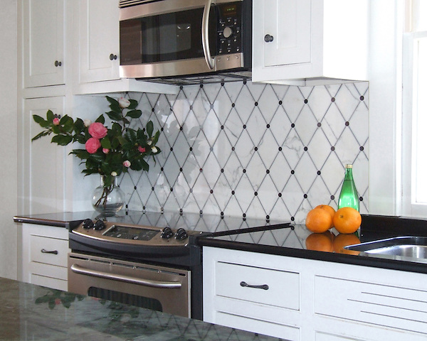 This custom kitchen features a handmade Quilt mosaic backsplash shown in Calacatta Tia, Nero Marquina, and Bardiglio from New Ravenna.<br />