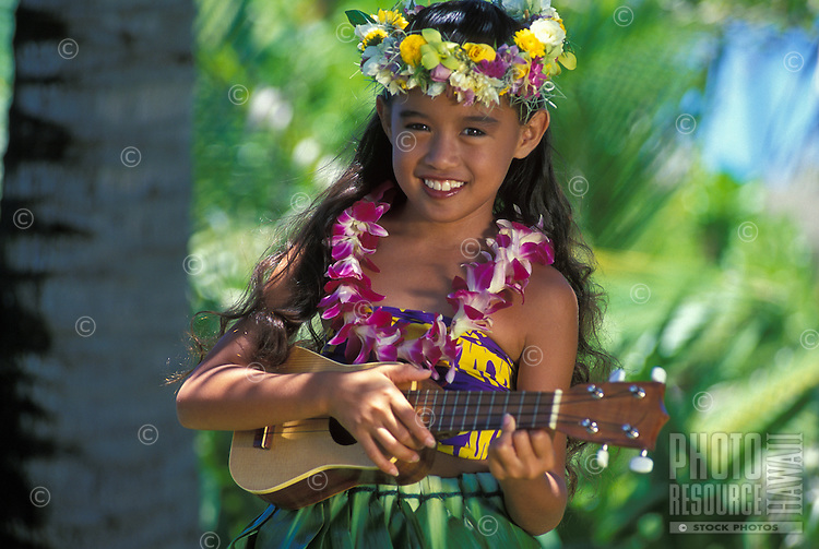 Beautiful Hawaiian girl (age 7) playing ukulele with orchid lei and haku lei on head