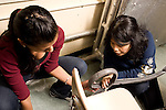 Education High School physics science lab two female students working together setting up experiment on rolled marble trajectory,  creating track