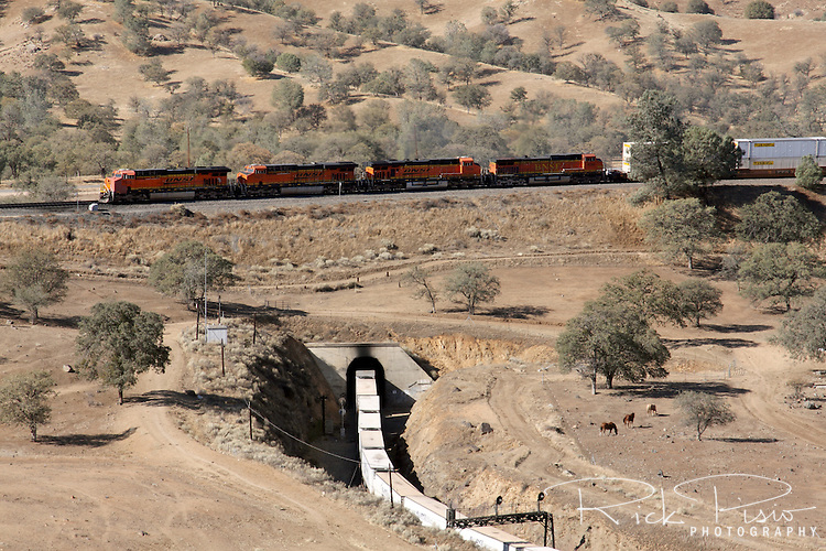 An eastbound BNSF freight train climbs and passes over itself at the Tehachapi Loop between Bakersfield and Mojave, California. The Tehachapi Loop is a .73 miles (1.17 km) long 'spiral', or helix, on the railroad main line. A train more than 4,000 feet (1.2 km) long (about 85 boxcars) will pass over itself going around the loop. In 1998 it was named a National Historic Civil Engineering Landmark.