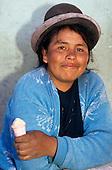 Uros, near Puno, Peru. Woman wearing traditional hat eating a meringue cone sweet.