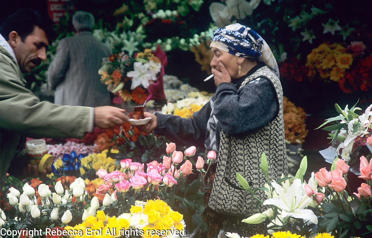 Gypsy flowerseller being handed tea, Taksim Square, Istanbul, Turkey