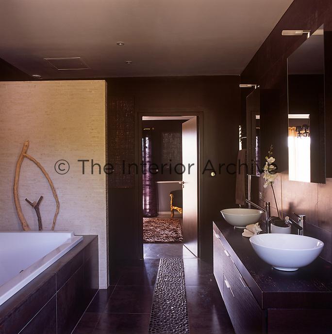 A modern bathroom with two washbasins set on a cupboard unit.