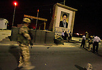 A British Army translator (2R) speaks with Iraqi Police as members of the Royal Air Force Regiment 1 Squadron pass a check-point at Basra Arches while they carry out a night patrol on the perimeter of Basra Airport Base in southern Iraq, in the early hours of 12 October 2005, ahead of the constitutional referendum on 15 October. The RAF Regiment is tasked with protecting airbases and other RAF assets around the world. AFP PHOTO / JOHN D MCHUGH