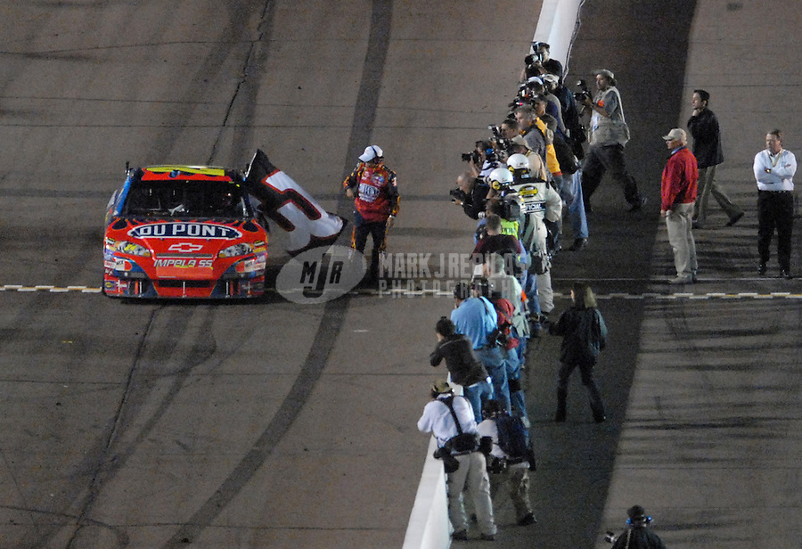Apr 21, 2007; Avondale, AZ, USA; Nascar Nextel Cup Series driver Jeff Gordon (24) gets a Dale Earnhardt Sr flag from a crew member after winning the Subway Fresh Fit 500 at Phoenix International Raceway. With the win Gordon tied the late Earnhardt Sr for career wins at 76. Mandatory Credit: Mark J. Rebilas