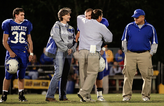 Head coach Mike Holcomb hugs senior Will Thomas Collins at Breathitt County High School's senior night in Jackson, Ky., on Friday Oct. 14, 2011. His brother Jon Keith Collins; mother, Betty; and father and coach, Jon Collins; watch Holcomb hug Will Thomas Collins on the field. Will Thomas, No. 7, is a running and defensive back for the Bobcats.  Photo by Rachel Aretakis