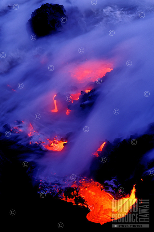 Fiery lava flows into the ocean creating clouds of steam at Volcanoes National park on the Big Island of Hawaii