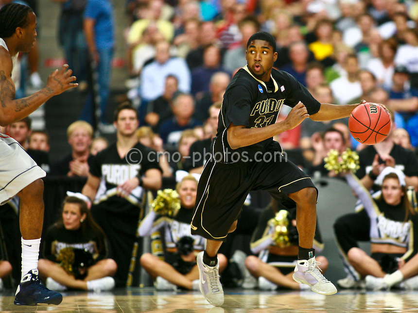 Mar 26, 2009; Tucson, AZ, USA; Connecticut Huskies forward Stanley Robinson (21) tries to defend the dribble of Purdue Boilermakers guard E'Twaun Moore (33) in the first half of a game in the semifinals of the west region of the 2009 NCAA basketball tournament at University of Phoenix Stadium.    UConn defeated Purdue 72-60.