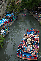 People eating at a restaurant on the riverwalk, River Walk Paseo del Rio, in San Antonio, South of Texas, USA, United States. There are a lot of restaurants along the river and the people can eat under colorful umbrellas. The best way to discover the city of San Antonio is to sail on the River with a motorboat.