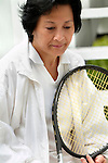 Asian woman holding tennis racket, looking thoughtful