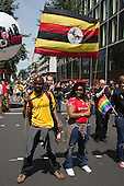 "29 June 2013, London, United Kingdom. Pictured: two people with Uganda shirts and a flag of Uganda. Pride London 2013 parade starts with the motto ""love (and marriage)""."
