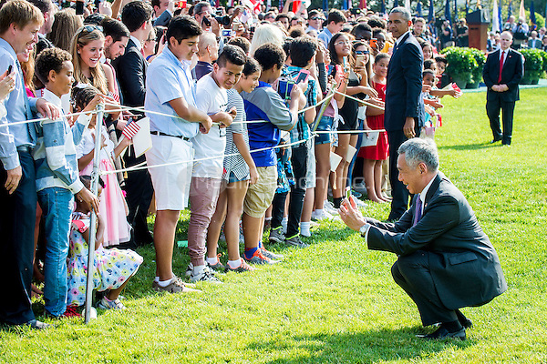 Prime Minister Lee Hsien Loong of Singapore takes a photo of a little girl while greeting guests during official welcoming ceremonies on the South Lawn of the White House in Washington, DC on August 2, 2016. Lee is on a State Visit to the United States.  <br /> Credit: Pete Marovich / Pool via CNP/MediaPunch