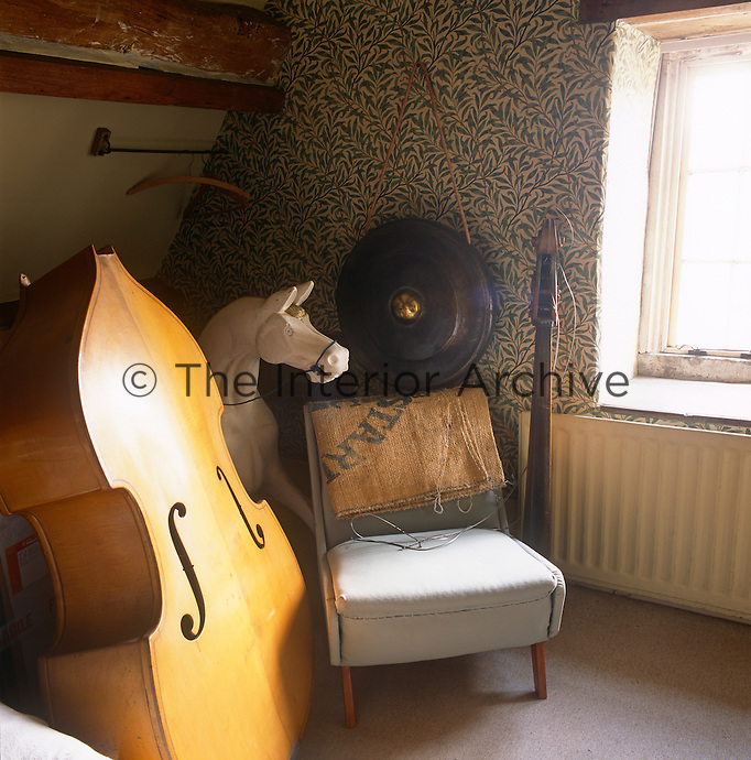 A detail of an attic bedroom decorated in William Morris pattern wallpaper. The body of a cello stands against a chair.